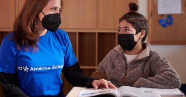 Niño sonriendo y mujer de fundación en Chile - América Solidaria